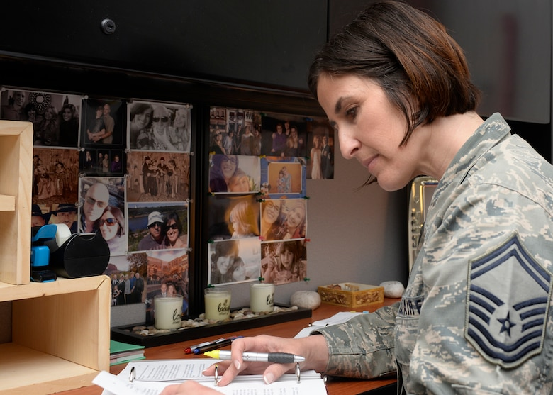 Senior Master Sgt. Laurice Souron, the inspector general from the 157th Air Refueling Wing, works in her office filled with photos of her children at Pease Air National Guard Base, N.H. April 27, 2017. (U.S. Air National Guard photo by Airman Victoria Nelson)