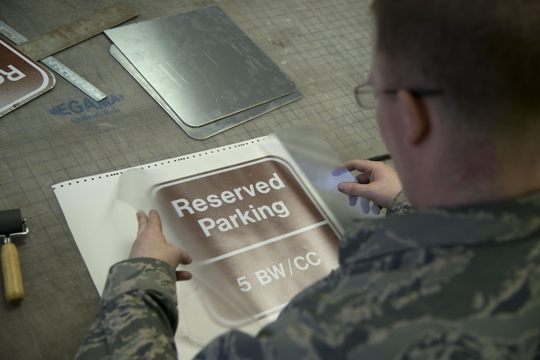 Staff Sgt. Horace Hand, 5th Civil Engineer Squadron structural craftsman, applies transfer paper to a sign at the sign shop on Minot Air Force Base, N.D., April 27, 2017. The sign shop produces about 20-25 signs per week. (U.S. Air Force photo/Airman 1st Class Dillon Audit)