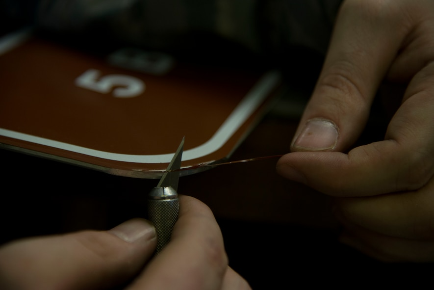 Staff Sgt. Horace Hand, 5th Civil Engineer Squadron structural craftsman, cuts excess vinyl from a sign at the sign shop on Minot Air Force Base, N.D., April 27, 2017. Hand uses a small sculpting knife to cut overlapping vinyl from the sign's edges. (U.S. Air Force photo/Airman 1st Class Dillon Audit)