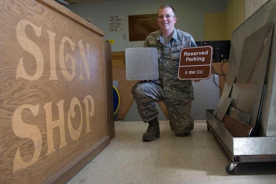Staff Sgt. Horace Hand, 5th Civil Engineer Squadron structural craftsman, presents a completed sign at Minot Air Force Base, N.D., April 27, 2017. The sign shop maintains all government signs on base and within the missle complex. (U.S. Air Force photo/Airman 1st Class Dillon Audit)