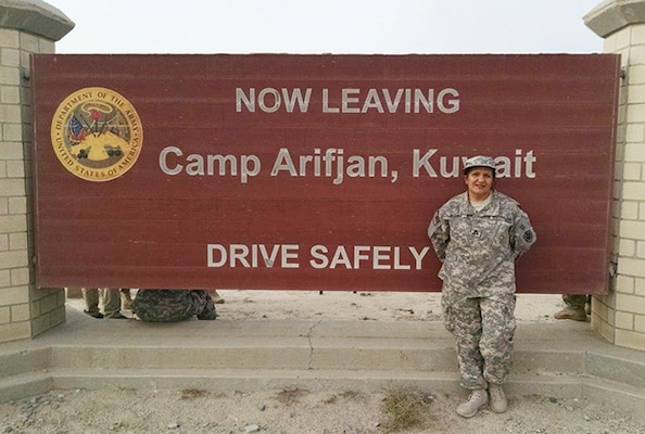 Amelia Stanko, contracting officer, Supply Operations Commodities Directorate, Defense Logistics Agency Aviation, poses next the exit sign for Camp Afrifjan, Kuwait as she ends her DLA Support Team deployment July 26, 2015.