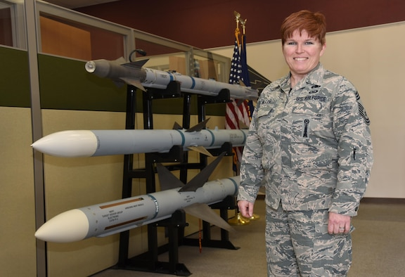 Oregon Air National Guard Chief Master Sgt. Kristen Miller pauses for a photograph next to a display of weapons in her work area at the 142nd Fighter Wing, Portland Air National Guard Base, Ore., May 7, 2017. Miller recently was appointed as the first female Chief Master Sergeant Munitions System Specialist Superintendent in the Air National Guard. (U.S. Air Force photo by Tech. Sgt. John Hughel)
