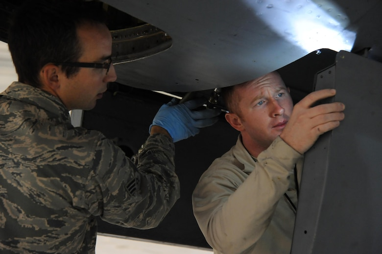 Airman 1st Class Jordan Brinkle, 22nd Aircraft Maintenance Squadron crew chief, right, and Senior Airman Andrew Colson, 931st Maintenance Group crew chief inspect a hinged door on the undercarriage of a KC-135 Stratotanker, Oct. 29, 2015, at McConnell Air Force Base, Kan. Maintenance Airmen ensure McConnell's aircraft are always ready to respond thereby enabling rapid global mobility daily. (U.S. Air Force photo/Airman Jenna K. Caldwell)