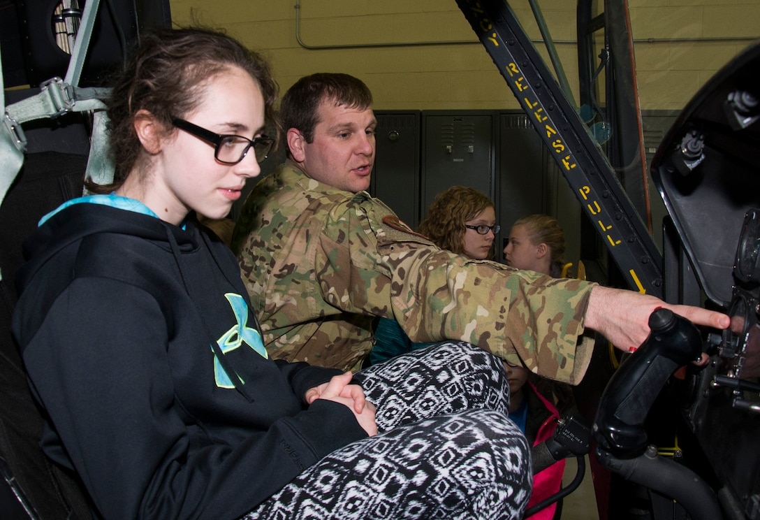 Capt. Alexander Kiel, 54th Helicopter Squadron chief of current operations, explains a helicopter's controls at Minot Air Force Base, N.D., May 1, 2017. During the tour, Edison Elementary School's science, technology, engineering and math girls visited a B-52H Stratofortress static display, the Missile Procedures Trainer, 5th Medical Group, 5th Civil Engineer Squadron fire station and the 54th Helicopter Squadron. (U.S. Air Force photo/Airman 1st Class Alyssa M. Akers)