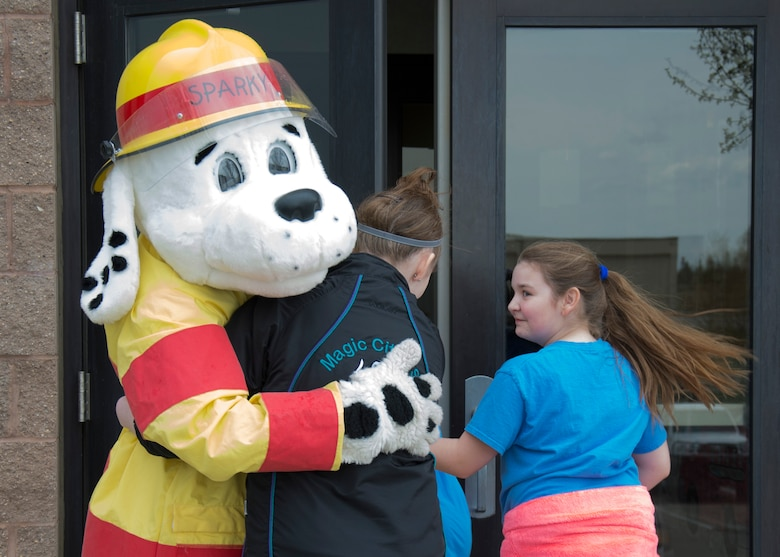 Sparky the Fire Dog, 5th Civil Engineer Squadron fire prevention educator, greets Edison Elementary School's science, technology, engineering and math girls at the 5th CES fire station on Minot Air Force Base, N.D., May 1, 2017. During the STEM girls' visit to the fire station, Sparky taught them about fire safety and basic firefighter duties. (U.S. Air Force photo/Airman 1st Class Alyssa M. Akers)