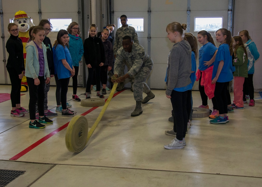 Staff Sgt. Shawn Vrock, 5th Civil Engineer Squadron crew chief, rolls a hose at the 5th CES fire station on Minot Air Force Base, N.D., May 1, 2017. Edison Elementary School's science, technology, engineering and math girls received a firehouse tour and learned basic firefighter duties. (U.S. Air Force photo/Airman 1st Class Alyssa M. Akers)