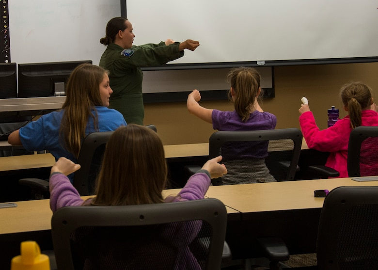 1st Lt. Katelyn Woodley, 741st Missile Squadron intercontinental ballistic missile combat crew commander, teaches Edison Elementary School's science, technology, engineering and math girls to launch a missile at the Missile Procedures Trainer on Minot Air Force Base, N.D., May 1, 2017. The STEM girls learned the basics of a missileer's job, including the necessary procedures of a missile launch. (U.S. Air Force photo/Airman 1st Class Alyssa M. Akers)