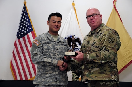 Spc. Kenny Ochoa, a watercraft operator with the 481st Transportation Company, is awarded by Command Sgt. Maj. Donald E. Langworthy II, interim command sergeant major of the 79th Sustainment Support, during the BWC's closing ceremony hosted by the 79th SSC at Camp Pendleton, Calif., May 6, 2017.  The U.S. Army Reserve's 79th Sustainment Support Command hosted their 2017 Best Warrior Competition at Camp Pendleton, Calif., May 3-6. The Best Warrior Competition seeks out the best candidate that defines a U.S. Army Soldier by testing Soldiers physically and mentally. The competition consisted of one enlisted Soldier and one noncommissioned officer from four separate one-star commands, which fall underneath the command and control of 79th SSC. At the conclusion, Ochoa was named one of the 79th SSC Best Warriors and will represent the command in the U.S. Army Reserve Best Warrior Competition held at Fort Bragg, N.C., June 4-10, 2017. (U.S. Army photo by Sgt. Heather Doppke/released)