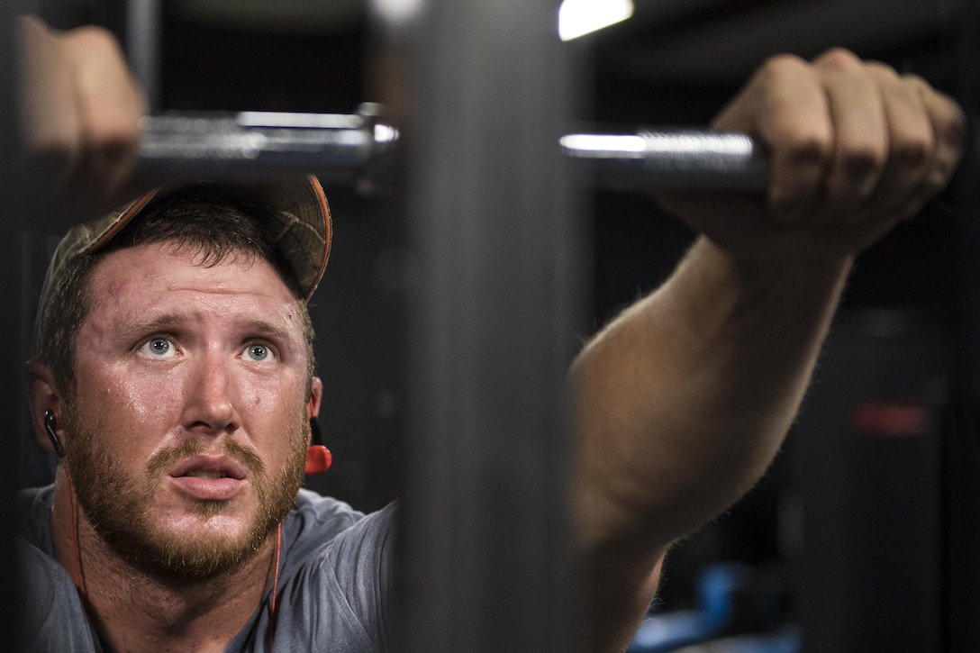 """Staff Sgt. Nicholas Worley, 23d Civil Engineer Squadron electrical systems craftsman, pauses during a workout, April 18, 2017, in Valdosta, Ga. In January 2012 Worley was diagnosed with Chronic Myelogenous Leukemia, an uncommon form of blood-cell cancer that starts in the blood-forming bone marrow cells. He's currently in remission and goes to the cancer center every three months to ensure his treatment is still working. """"The gym plays a major part in my remission status because I can see my body progressing and getting stronger and I know I'm not feeling sick,"""" said Worley. (U.S. Air Force Photo by Senior Airman Janiqua P. Robinson)"""