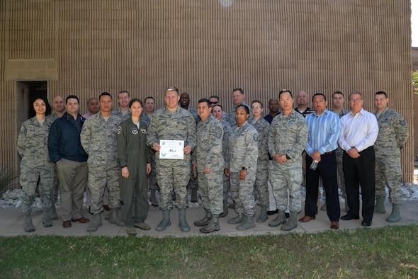 "Senior Airman Justin Merritt, 47th Contracting Flight contract specialist (center), accepts the ""XLer of the Week"" award from Col. Michelle Pryor, 47th Flying Training Wing vice commander (left), and Chief Master Sgt. George Richey, 47th FTW command chief (right), on Laughlin Air Force Base, Texas, May 1, 2017. The XLer is a weekly award chosen by wing leadership and is presented to those who consistently make outstanding contributions to their unit and Laughlin. (U.S. Air Force photo/Technical Sgt. Mike Meares)"