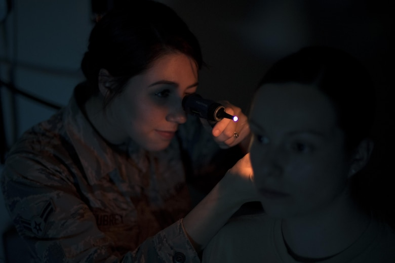 Senior Airman Kristen Aubrey, 23d Medical Operations Squadron aerospace medical technician, inspects a simulated patient's ear, May 4, 2017, at Moody Air Force Base, Ga. After recognizing a patient with life-threatening symptoms, Aubrey was honored for quickly responding to a potentially dire situation. (U.S. Air Force photo by Airman 1st Class Daniel Snider)