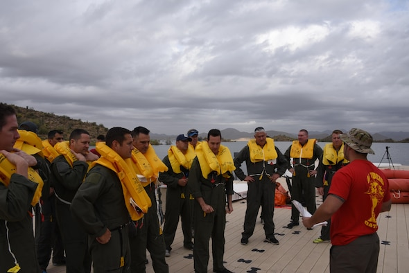 Tech. Sgt. Matthew Duncan, an aircrew flight equipment specialist assigned to the 161st Air Refueling Wing, teaches KC-135 Stratotanker aircrew members how to don their life preservers and board a 20-man life raft to prepare for rescue at Lake Pleasant aquatic center, Ariz., May 7, 2017. Water survival training is conducted every two years at the wing to refresh the aircrew on using the life support equipment on board the aircraft in the event of an emergency. (U.S. Air Force photo by Tech. Sgt. Michael Matkin)