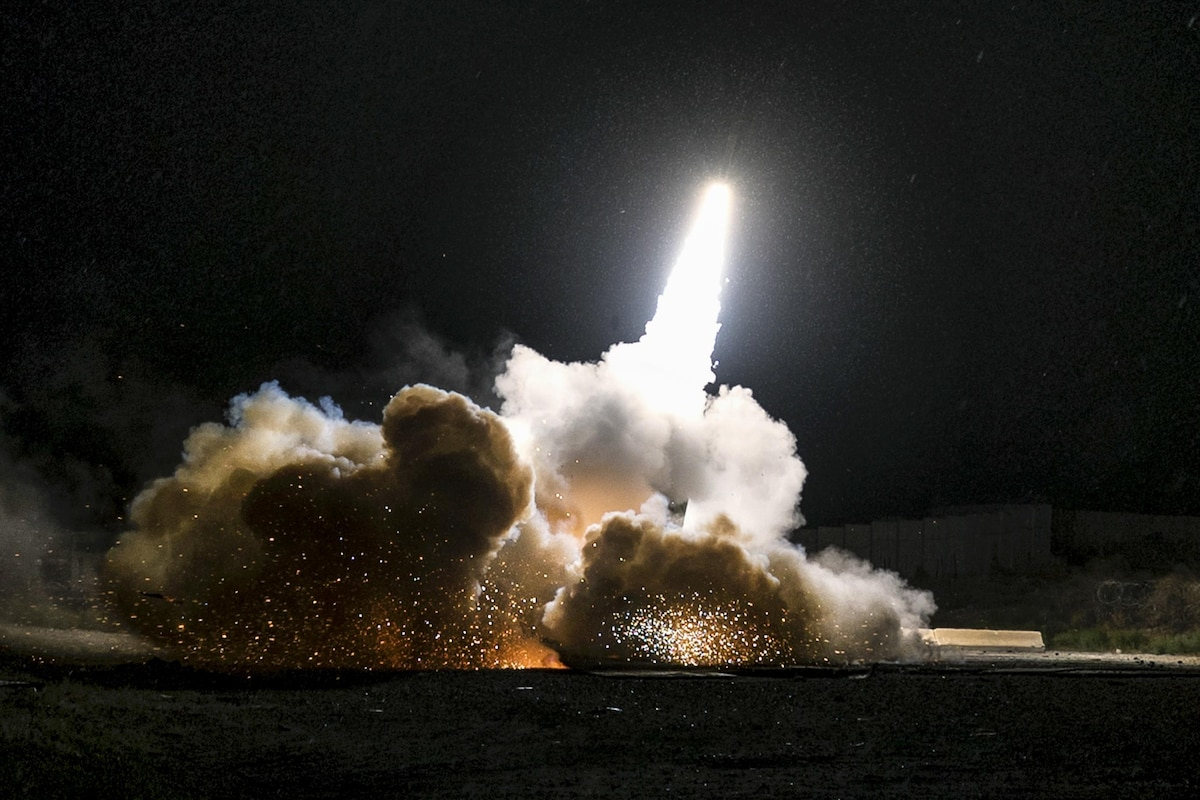 A rocket launching at night surrounded by clouds of smoke.
