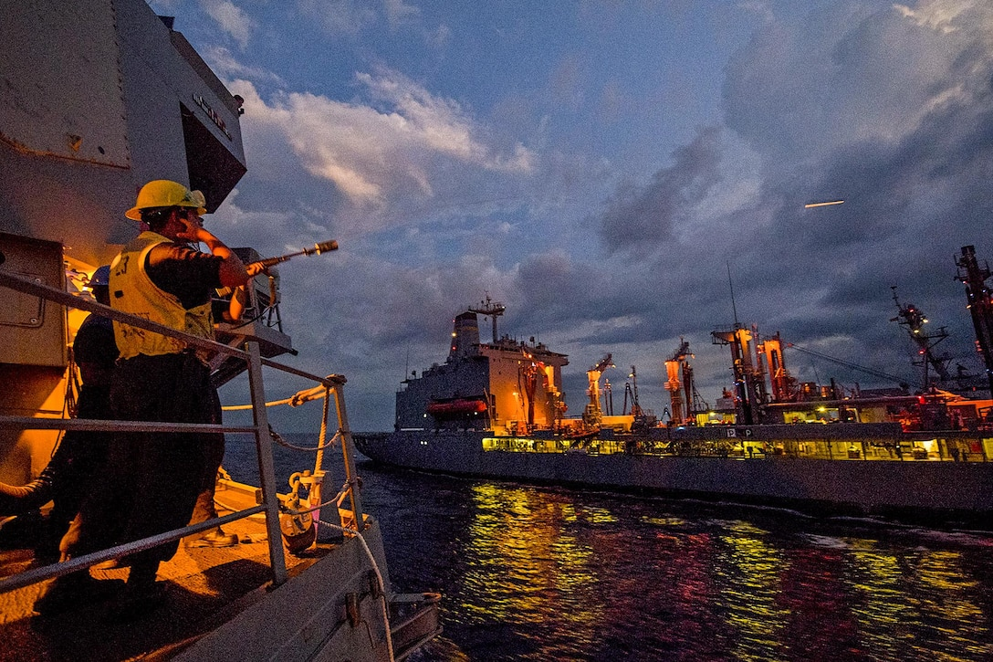 Navy Petty Officer 1st Class Darwin Williams fires a shot line from the USS Sterett to the USNS John Ericsso.