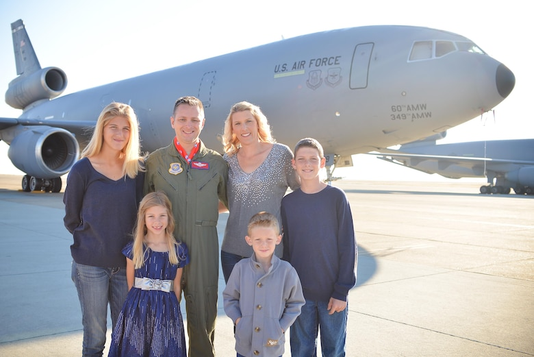 Chief Master Sgt. Rob Wellbaum, 15th Operations Group superintendent, and his family pose in front of a KC-10 Extender.  (Courtesy Photo)