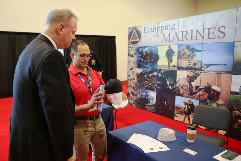 Mark Urrutic, project officer for Family of Field Medical Equipment Team at Marine Corps Systems Command, uses an Infrascanner to locate a simulated hematoma on a mannequin's skull while MCSC's Executive Director William Williford looks on at the Navy League's Sea Air Space Exhibition in National Harbor, Maryland, on April 3. The Infrascanner is a portable, medical diagnostic device that provides early detection of intracranial hematomas-or bleeding within the skull-in the field, potentially saving lives and improving casualty care and recovery. (U.S. Marine Corps photo by Ashley Calingo)