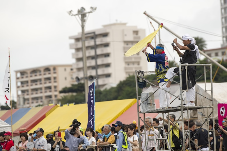 Spectators watch in anticipation as an official waves a flag, signaling the start of a heat during the Naha Dragon Boat Race May 5, 2017, at Naha Port, Japan. Months of hard work, long practices and extensive conditioning goes into competing for the Kadena Shoguns men's and women's dragon boat teams each year for the more than 30 members on each team. (U.S. Air Force photo by Senior Airman Omari Bernard)
