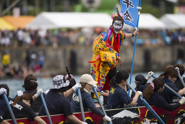 A dragon boat team member dressed in Ryuku traditional garb cheers on her teammates during the Naha Dragon Boat Race May 5, 2017, at Naha Port, Japan. The dragon boat teams, composed of 32 rowers, board long fiberglass boats painted to resemble mythical seafaring dragons. The race lasts less than 5 minutes as teams push their bodies to the limit. (U.S. Air Force photo by Senior Airman Omari Bernard)