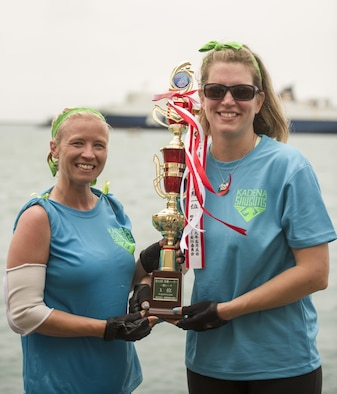 Jessica Bone and Sherry Sawyer, Kadena Shoguns's Women's Dragon Boat Team members, hold up a trophy for placing first in their heat May 5, 2017, at Naha Port, Japan. The Kadena Shoguns Women's Dragon Boat Team defeated the Army's and Navy's women's dragon boat teams to defend their title of best military women's dragon boat team. (U.S. Air Force photo by Senior Airman Omari Bernard)