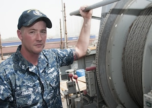 170509-N-XP344-033 MANAMA, Bahrain (May 9, 2017) Mineman 2nd Class Tyler Smith, a native of Munford, Ala. and assigned to the Avenger-class mine countermeasure ship USS Devastator (MCM 6), poses for a photo in front of Devastator's sweep line. On April 23, Smith deployed to the Avenger-class mine countermeasure ship USS Dextrous (MCM 13) and repaired the ship's swage, a thick metal clasp that secures the ship's sweep wire and withstands up to 18,000 pounds of pressure. (U.S. Navy photo by Mass Communication Specialist 2nd Class Victoria Kinney)