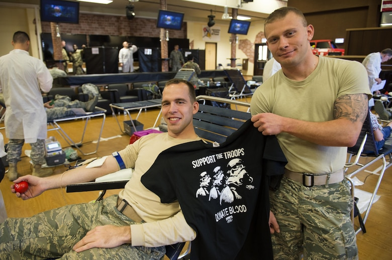 U.S. Air Force Airman 1st Class Ian Christner and Senior Airman Allen Turner, both 52nd Civil Engineer Squadron heavy equipment operators, pose with a Star Wars themed blood donor shirt during an Armed Services Blood Program blood drive in the Brick House at Spangdahlem Air Base, Germany, May 10, 2017. The ASBP is the official blood collection, manufacturing and transfusion program for the U.S. military.
