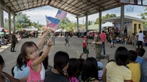 A little girl waves Philippine and U.S. flags during a basketball game at a Balikatan 2017 community relations event, at Margen Elementary School in Ormoc, Leyte, May 2, 2017. Balikatan is an annual U.S.-Philippine bilateral military exercise focused on a variety of missions, including humanitarian assistance and disaster relief, counterterrorism, and other combined military operations.