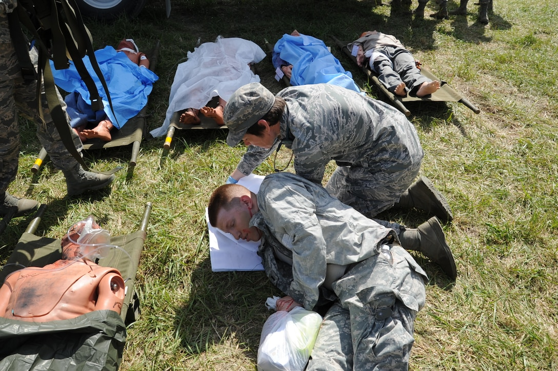 Lt. Col. Candy Wilson, 779th Medical Group chief nurse, sets a pillow under the head of an actor posing as a patient injured April 26, 2017 at Camp Atterbury, Ind. The actor portrayed a patient suffering from a head injury and body lacerations resulting from a mock nuclear attack that occurred within the U.S. (U.S. Air Force photo by Staff Sgt. Joe Yanik)