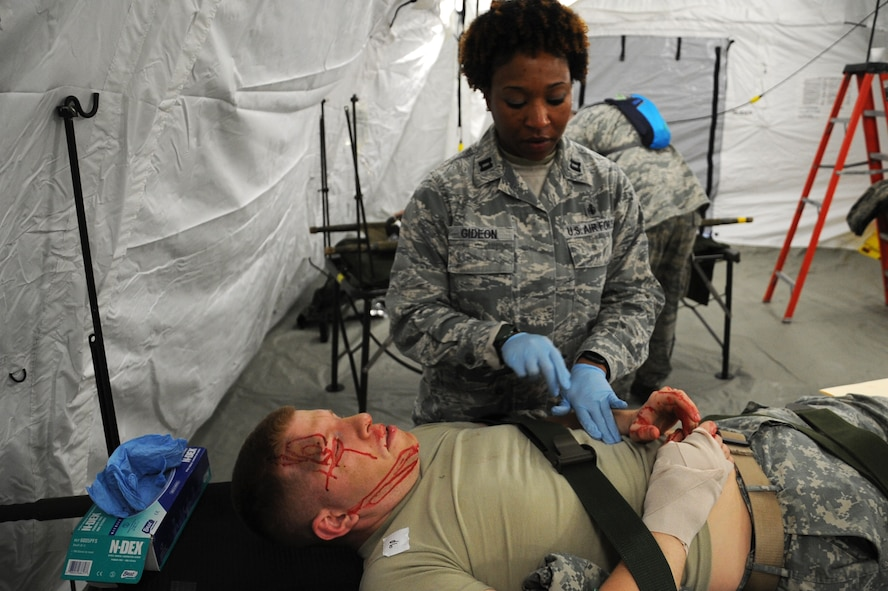 Capt. Falana Gideon (standing), 779th Medical Group ward nurse, simulates checking for internal injuries by pressing the abdomen of an actor posing as a casualty from a mock nuclear attack April 25, 2017, at a Emergency Medical Support facility, Camp Atterbury, Ind. Air Force nurses, like Gideon, must have bachelor's degrees in nursing from accredited schools whose programs include classroom instruction and supervised clinical work. (U.S. Air Force photo by Staff Sgt. Joe Yanik)