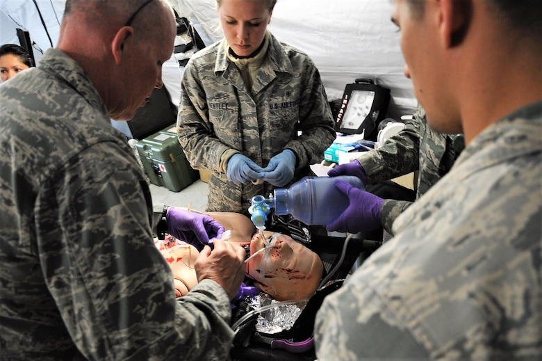 Maj. Richard Odosso (left) 779th Medical Group nurse, adjusts the air tubes inserted into a dummy portraying a wounded patient at the group's Emergency Medical Support facility April 28, 2017 at Camp Atterbury, Ind. Unlike civilian nurses, military nurses like Odosso are trained to treat patients during aeromedical evacuation missions and in deployed settings. (U..S. Air Force photo by Staff Sgt. Joe Yanik)