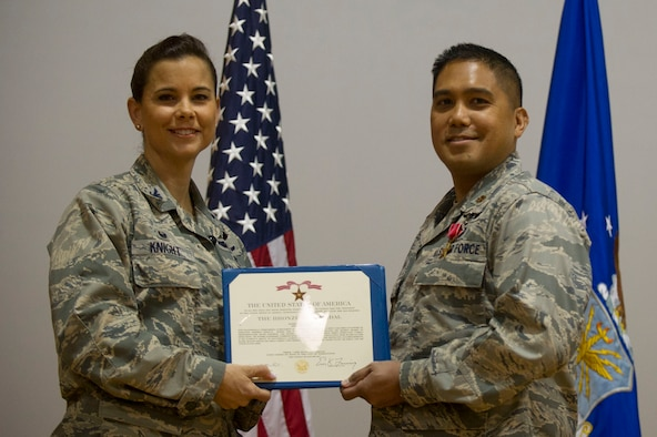 Col. Leslie Knight, 779th Medical Group commander, and recent Bronze Star recipient Maj. Dino Quijano, a critical care nurse, display Maj. Quijano's citation. The Air Force is recognizing the contributions of nurses and medical technicians during National Nurses and Technicians week. (Photo by Senior Master Sgt. Adrian Cadiz)(Released)