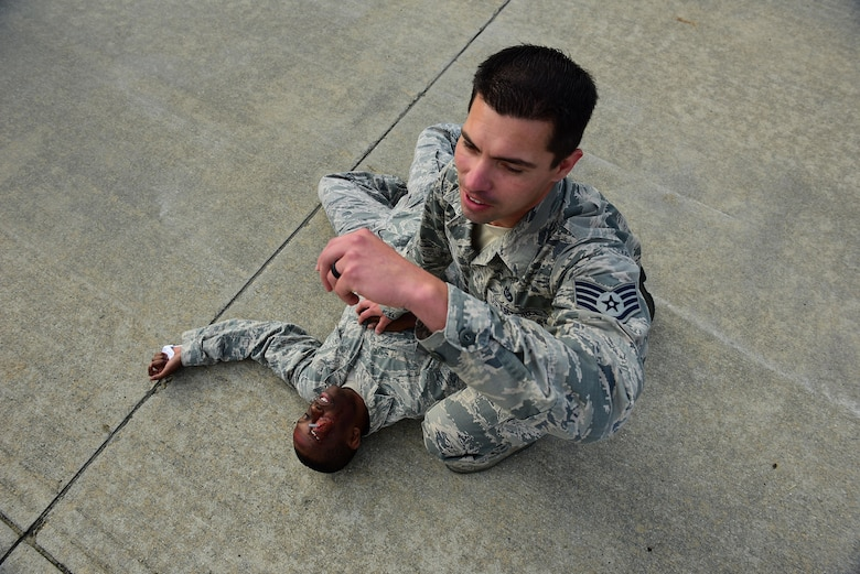 Staff Sgt. William B. Silva, 4th Civil Engineer Squadron unit deployment manager (right), calls out to emergency medical responders to help Airman 1st Class Mark Mugo, 4th Civil Engineer Squadron operations management technician, during a Major Accident Response Exercise, May 10, 2017, at Seymour Johnson Air Force Base, North Carolina. Mugo simulated injuries to test and improve first responders' capabilities. (U.S. Air Force photo by Airman 1st Class Kenneth Boyton)