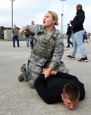 Senior Airman Paige E. Johnson, 4th Security Forces Squadron patrolman, apprehends simulated stabbing suspect, Senior Airman Alexander Ritsema, 4th Maintenance Group weapons standardization technician, as another participant prepares to detonate a simulated bomb vest, during a Major Accident Response Exercise, May 10, 2017, at Seymour Johnson Air Force Base, North Carolina. During the exercise members from the 4th Security Forces Squadron detained the suspect, evacuated the scene and set up a perimeter around the area. (U.S. Air Force photo by Airman 1st Class Victoria Boyton)