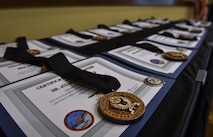 Certificates and medallions sit on display at Air Force Special Operations Command's 2016 Outstanding Airmen of the Year at Hurlburt Field, Fla., May 10, 2017. AFSOC formally recognized its outstanding Airmen of the year with a weeklong tour of Hurlburt Field. (U.S. Air Force photo by Airman 1st Class Joseph Pick)