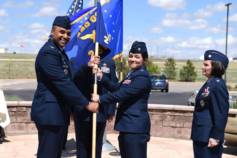 Col. Lorenzo Bradley, 460th Operations Group commander, hands the 2nd Space Warning Squadron guidon to Lt. Col. Shannon DaSilva, 2nd SWS commander, May 11, 2017, on Buckley Air Force Base, Colo.  Shannon, the squadron's new commander, is now responsible for the primary operations unit within the 460th OG. (U.S. Air Force photo by Airman 1st Class Holden S. Faul/Released)