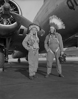 "B-17 Flying Fortress crewmembers Gus Palmer, a citizen of the Kiowa nation and a side gunner, and Horace Poolaw, also a Kiowa and an aerial photographer, stand near their aircraft at MacDill Field, Fla., in about 1944.  This photo is in the exhibition ""For a Love of His People: The Photography of Horace Poolaw,"" on the third floor of the National Museum of the American Indian. Photo courtesy of the estate of Horace Poolaw and the National Museum of the American Indian"
