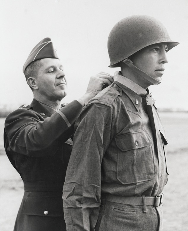 "Army 2nd Lt. Ernest Childers, from the Muscogee Creek nation, receives the Medal of Honor from Army Lt. Gen. Jacob L. Devers, at 5th Army headquarters in Italy, April 8, 1944. Childers, operating under heavy enemy fire, wiped out two German machine gun nests near Oliveto, Italy, killing enemy snipers and capturing an artillery observer. This photo is one of 24 panels displayed in the ""Patriot Nations"" exhibit on the second floor of the National Museum of the American Indian. Photo by Otto Bettmann, courtesy of the National Museum of the American Indian"