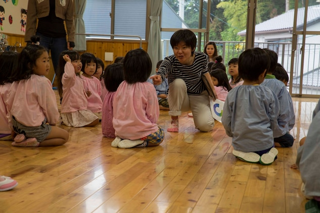"Shiori Minato, an administration specialist with the Marine Memorial Chapel, counts groups of Josho Hoikuen Preschool students during a community relations event in Iwakuni City, Japan, May 9, 2017. Volunteering at the preschool helped the relationship between Marine Corps Air Station Iwakuni residents and the local community grow stronger. Introductions were given by the volunteers while students asked them questions, then the children were introduced to ""The Hokey Pokey"" and ""Head, Shoulders, Knees and Toes"" before playing educational games with the volunteers. (U.S. Marine Corps photo by Lance Cpl. Gabriela Garcia-Herrera)"