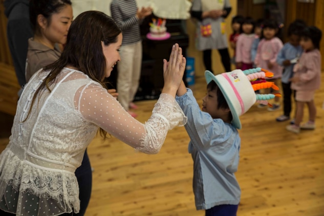 "Michelle Hena, a volunteer with the Marine Memorial Chapel, high-fives a Josho Hoikuen Preschool student after singing ""Happy Birthday"" to him during a community relations event in Iwakuni City, Japan, May 9, 2017. Volunteering at the preschool helped the relationship between Marine Corps Air Station  Iwakuni residents and the local community grow stronger. Introductions were given by the volunteers while students asked them questions, then the children were introduced to ""The Hokey Pokey"" and ""Head, Shoulders, Knees and Toes"" before playing educational games with the volunteers. (U.S. Marine Corps photo by Lance Cpl. Gabriela Garcia-Herrera)"