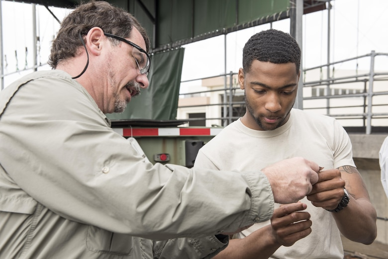 Larr Mudd, corrosion control trainer, shows U.S. Air Force Senior Airman Ladavian Varnes, 374th Logistics Readiness Squadron vehicle maintainer, a tool used to measure the thickness of applied solutions or paints to metal surfaces April 6, 2017, at Kadena Air Base, Japan. Varnes traveled from Osan Air Base to learn about and teach the 18 LRS's new vehicle corrosion control program. (U.S. Air Force photo by Senior Airman Omari Bernard)
