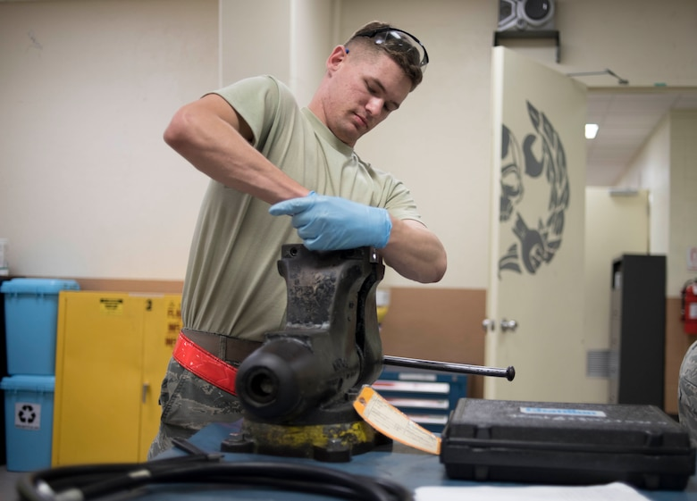 U.S. Air Force Senior Airman Joshua Cox, 18th Component Maintenance Squadron hydraulics technician, tightens a medium pressure rubber hose assembly May 2, 2017, at Kadena Air Base, Japan. Hydraulics Airmen often rely on several shifts in order to complete repairs in a timely fashion, such as having one shift disassembling and inspecting a part and the next shift reassembling and testing the part. (U.S. Air Force photo by Senior Airman John Linzmeier)