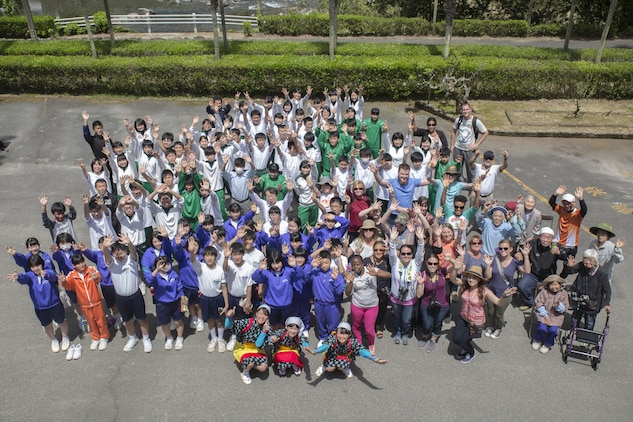 Marine Corps Air Station Iwakuni residents pose alongside Japanese students and locals duing a Cultural Adaption Program tea harvesting event in Iwakuni City, May 2, 2017. The Cultural Adaptation Program gave station residents the opportunity to experience the Japanese culture alongside elementary and high school students, nursing home residents and other Japanese locals. (U.S. Marine Corps photo by Lance Cpl. Carlos Jimenez)
