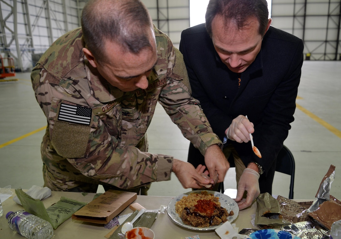 U.S. Air Force Col. Mark O'Reilly, 352nd Special Operations Maintenance Group commander, assists Rob Humphries, 352nd SOMXG honorary commander in creating a gourmet meal for a Meal Ready to Eat Bake-Off Competition for Honorary Commanders' Day, May 9, 2017, on RAF Mildenhall, England. Base leadership and honorary commander teams create main dishes, side dishes, desserts and drinks with two MREs. (U.S. Air Force photo by Senior Airman Christine Groening)