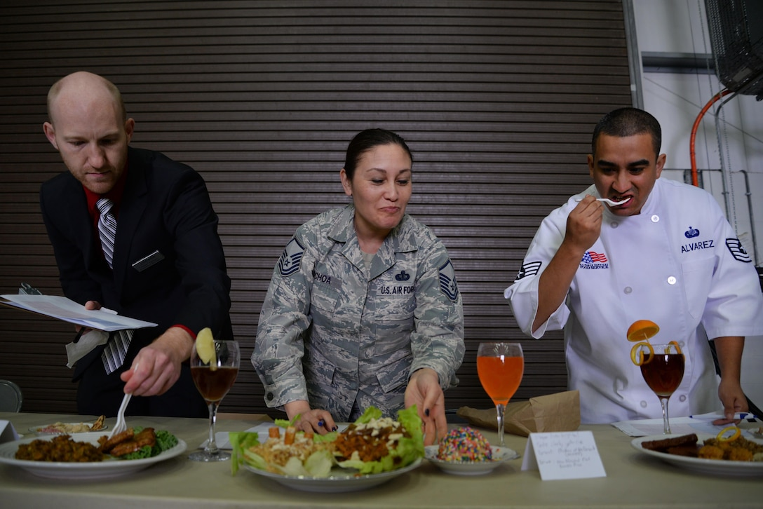 From left to right, David Barnes 100th Force Support Squadron Galaxy Club manager, U.S. Air Force Master Sgt. Mati Ochoa, 100th Air Refueling Wing NCO in charge of protocol, and Tech. Sgt. Andy Alvarez, 100th FSS Dining Facility assistant manager, test gourmet dishes created by base leadership and their honorary commanders May 9, 2017, on RAF Mildenhall, England. The three judged the meals created with Meal Ready to Eat packets based on the dishes' appearance, taste and creativity. (U.S. Air Force photo by Senior Airman Christine Groening)