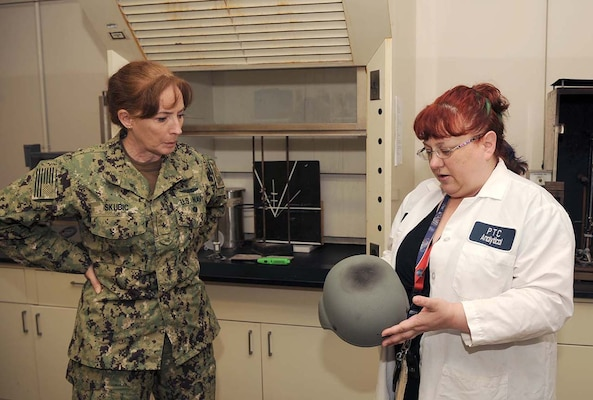 DLA Land and Maritime Commander Navy Rear Adm. Michelle Skubic (left) discusses the results of blunt force impact testing for helments with DLA Mechanicsburg lab technician Sally Schuster  during a site visit.
