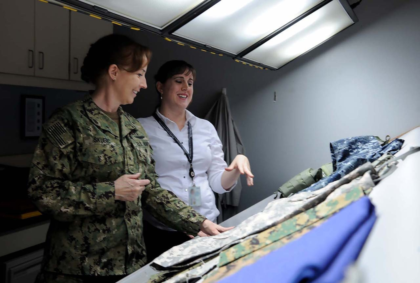 DLA Land and Maritime Commander Navy Rear Adm. Michelle Skubic (left) and Jamie Hieber, director of the Product Test Center Analytical Unit, review uniform materials in a shade lab during Skubics orientation visit.