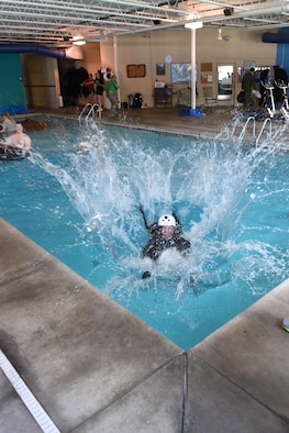 Lt. Col. Nicholas Zetocha, air sovereignty alert commander assigned to the 180th Fighter Wing, Ohio Air National Guard, crashes into the water after being dragged in to simulate an ejection landing May 6, 2017 during water survival training at the Aqua Hut in Toledo, Ohio. Constant training ensures Airmen maintain the highest standards and are ready for worldwide deployments at all times. (U.S. Air National Guard photo by Airman Hope Geiger)