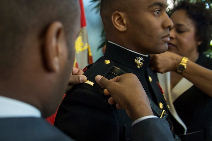 Second lieutenant Mitchell Harrison's mother and brother pin on the bars denoting his rank during a Commissioning Ceremony at Embry-Riddle Aeronautical University's College of Business in Daytona Beach, Florida, May 10, 2017. The ceremony commemorated Harrisons' commission as a second lieutenant in the Marine Corps. Harrison completed the 10-week long Officer Candidates School and is preparing to leave for The Basic School in July 2017. (U.S. Marine Corps photo by Lance Cpl. Jack A. E. Rigsby/Released)
