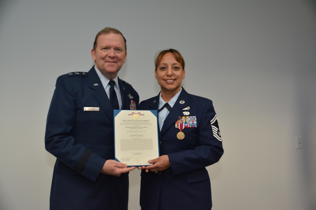 During his final commander's call, Major General Richard Scobee, Tenth Air Force Commander, presented the Meritorious Service Medal to Senior Master Sgt. Vickie Speece, Tenth Air Force Unit Training Superintendent, for outstanding achievement in support of ongoing contingency operations.