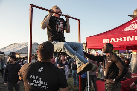 A Beale Street Music Festival attendee attempts a Marines pull-up in Memphis, Tennessee, May 6, 2017. Marines with Recruiting Substation Southaven conducted a pull-up challenge during the Memphis in May International Festival. (U.S. Marine Corps photo by Sgt. Mandaline Hatch)