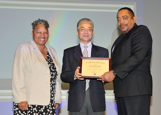 Ke Liu, M.D., receives a certificate of appreciation from DLA Chief of Staff Renee Roman and EEO and Diversity Director Ferdinand 'Leo' LeCompte April 10.